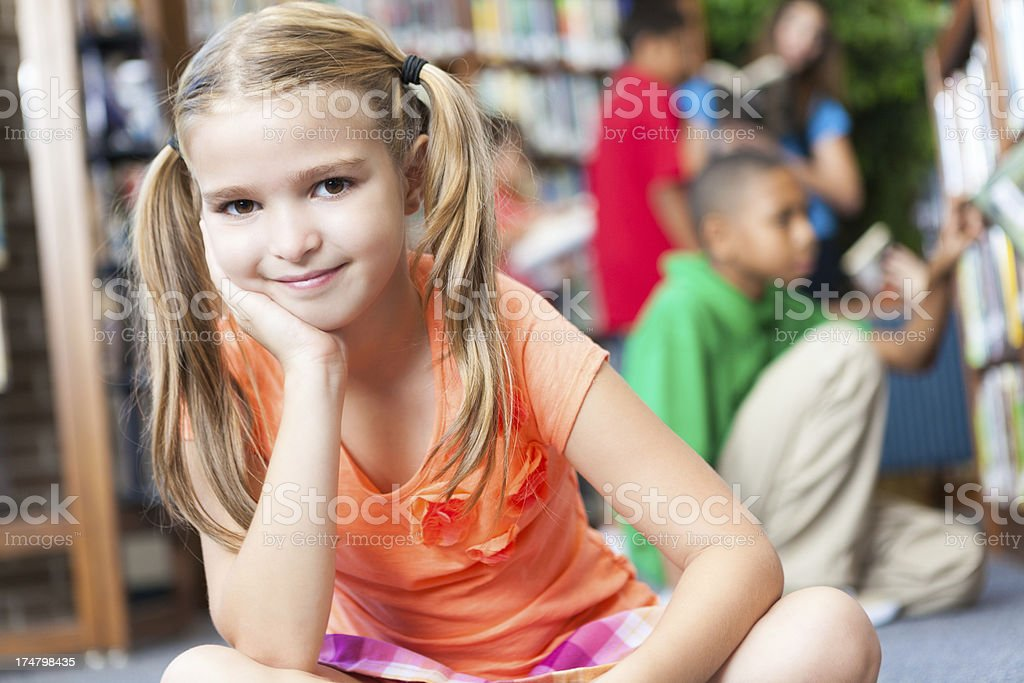 Little girl leaning in school library royalty-free stock photo