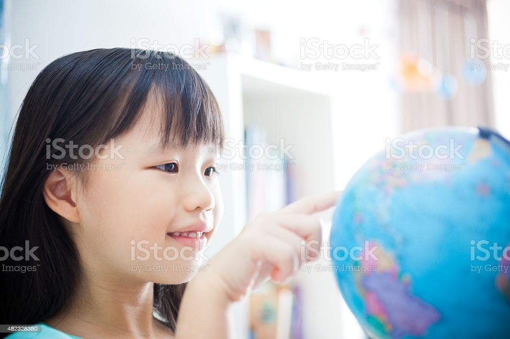 Little Girl Learning and Pointing at a Globe stock photo