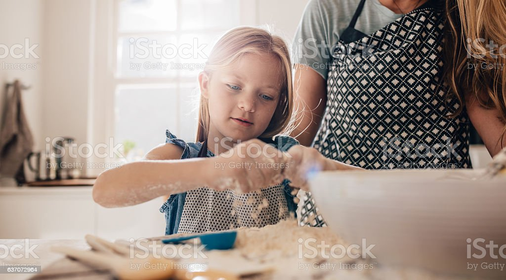 Little girl learning to cook stock photo