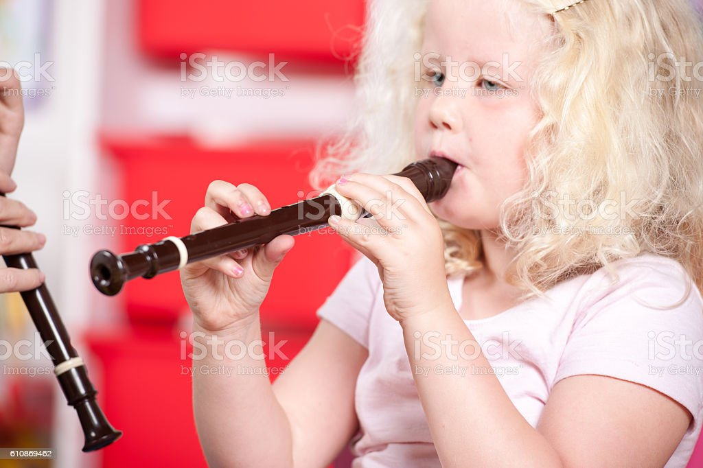 Little Girl Learning To Play Recorder stock photo