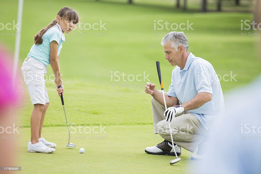 Little girl learning to putt during golf lesson with pro stock photo