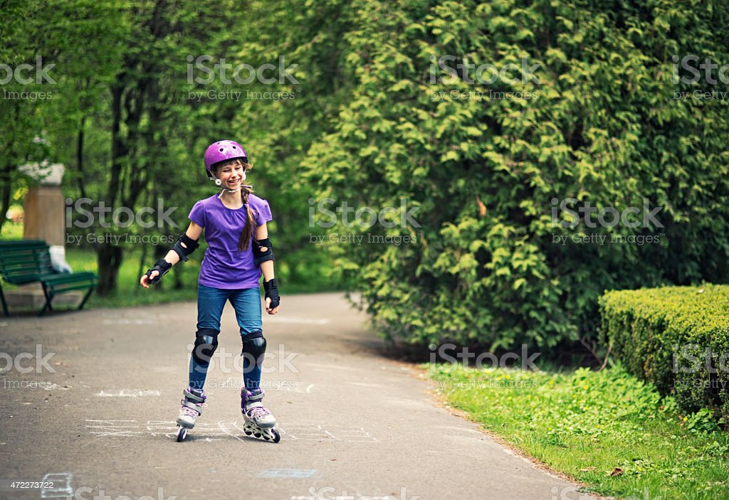 Little girl learning to rollerskate in park stock photo