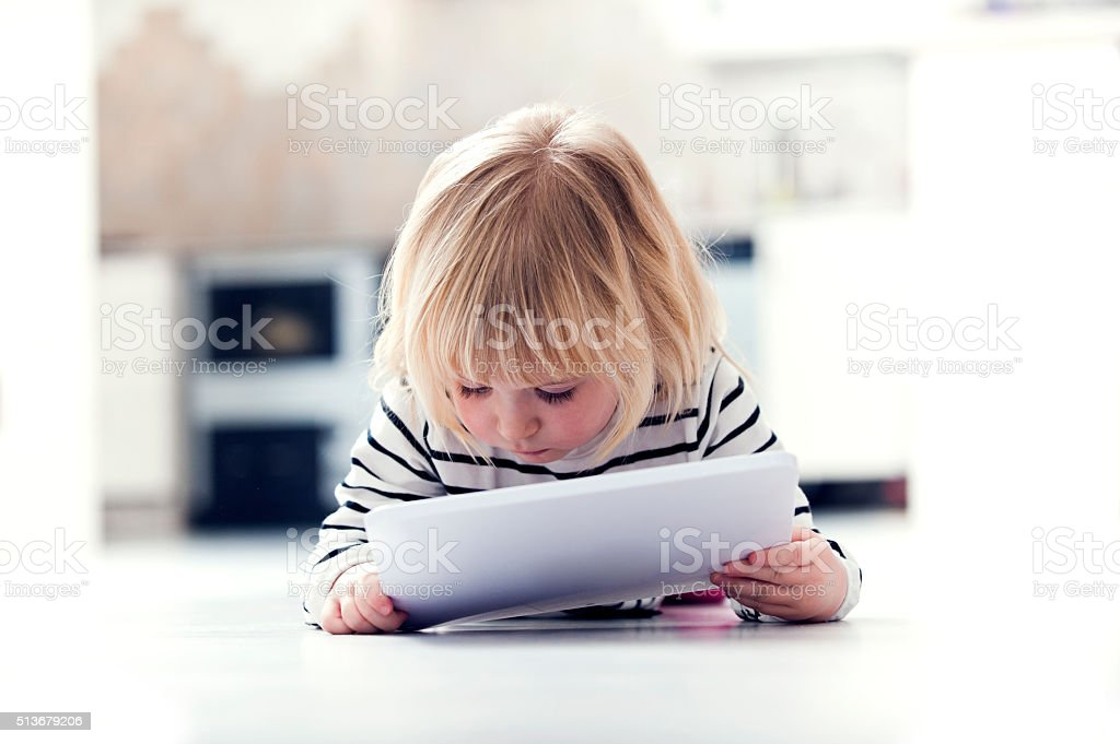 Little girl lying on floor learning using digital tablet at home