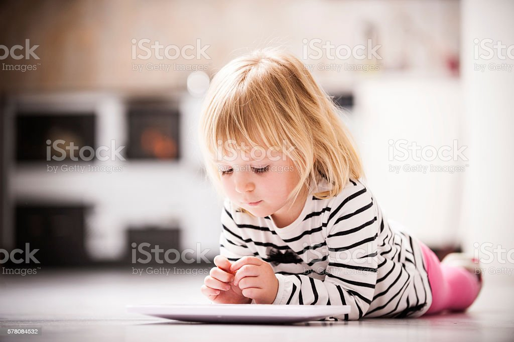 Little girl using digital tablet at home