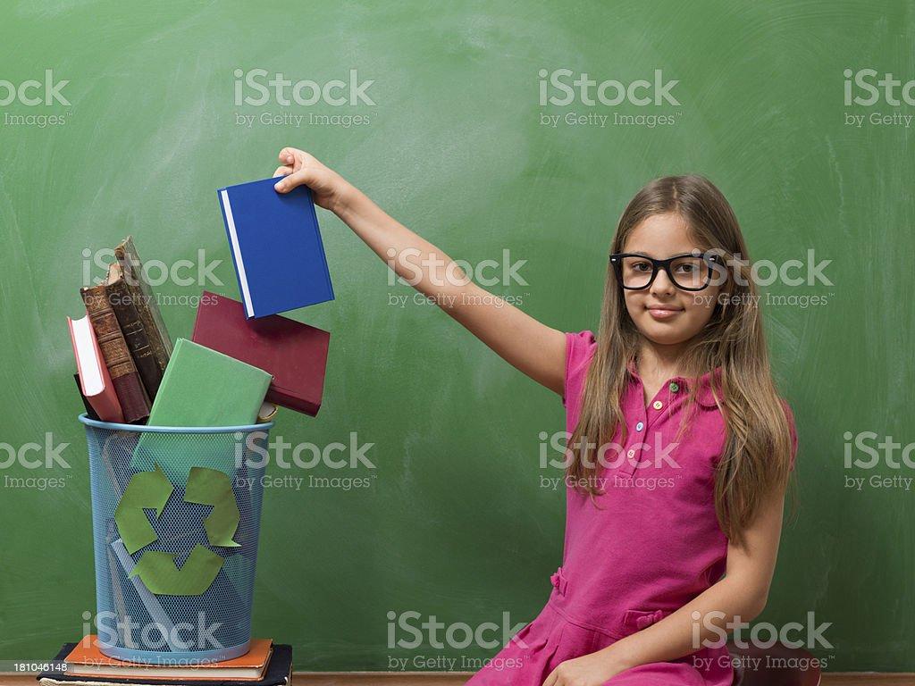 Little girl leaving book in recycling bin before blackboard royalty-free stock photo