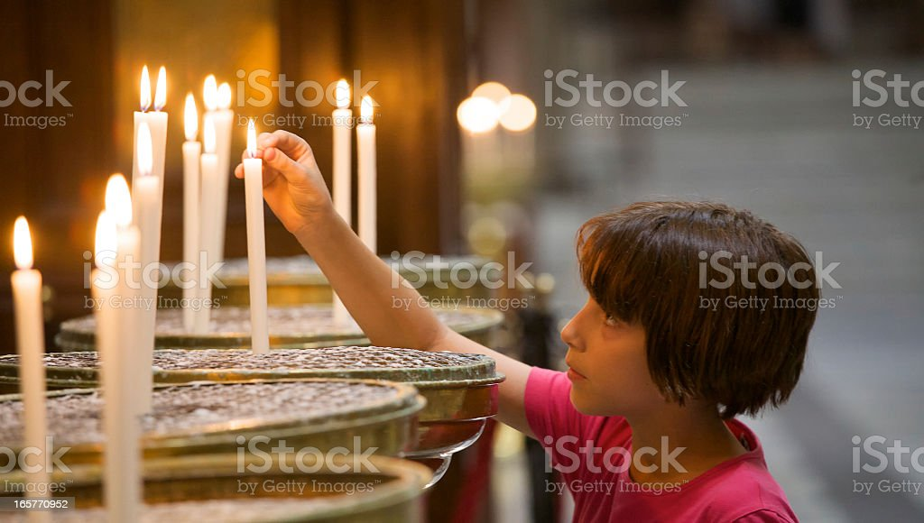 Little girl lighting a candle in church stock photo