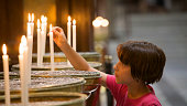 Little girl lighting a candle in church