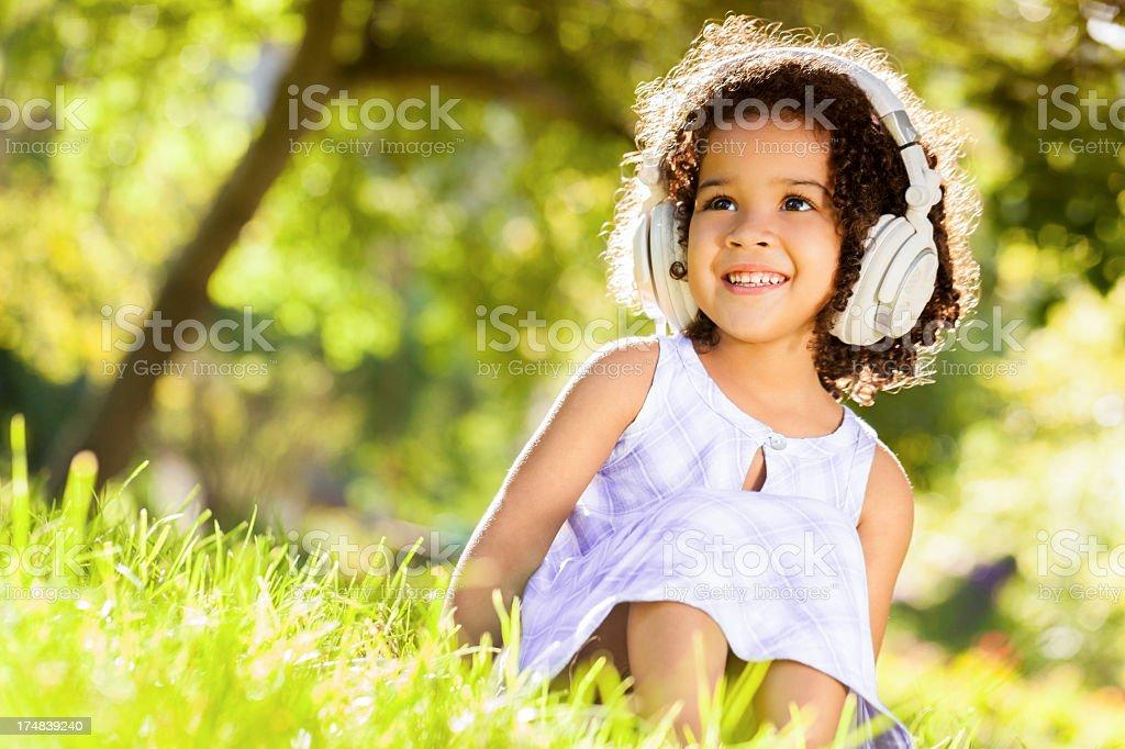 Little Girl Listening To Music In Garden royalty-free stock photo