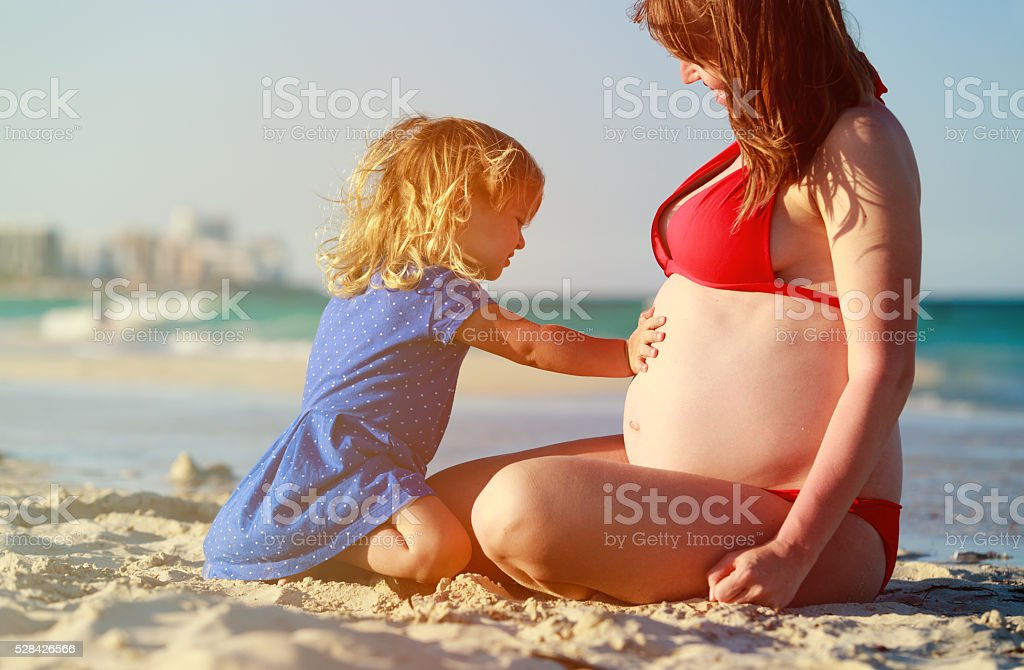 little girl listening to pregnant mother tummy at beach stock photo
