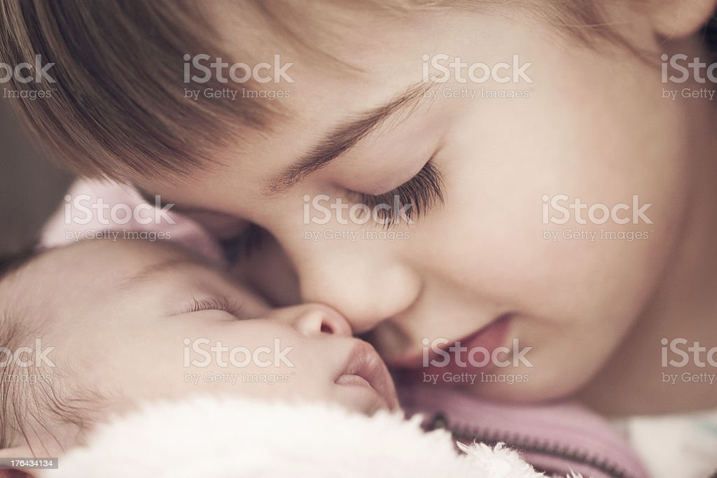 Little girl looking at a newborn baby stock photo