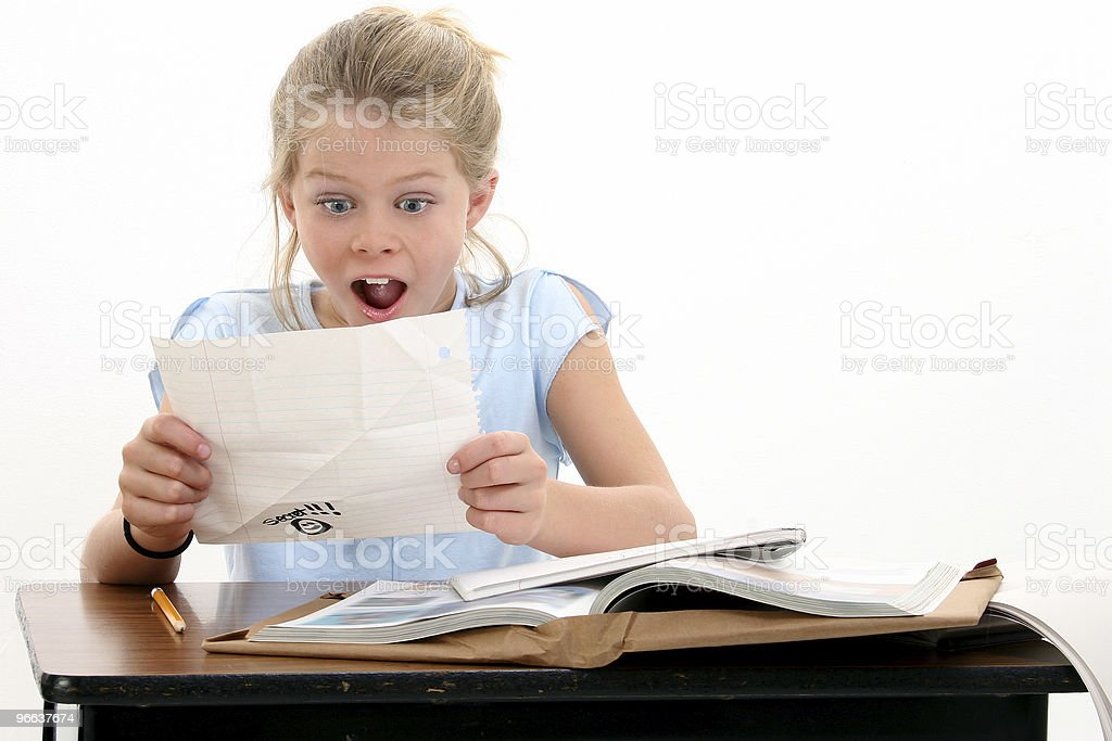 A little girl looking at a paper at her school desk royalty-free stock photo