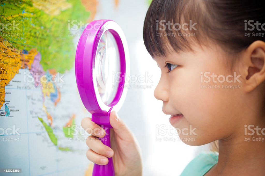 Little Girl Looking at a World Map with Magnifying Glass stock photo