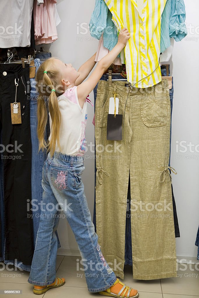 Little girl looking at adult's colorful  shirts in the store. stock photo
