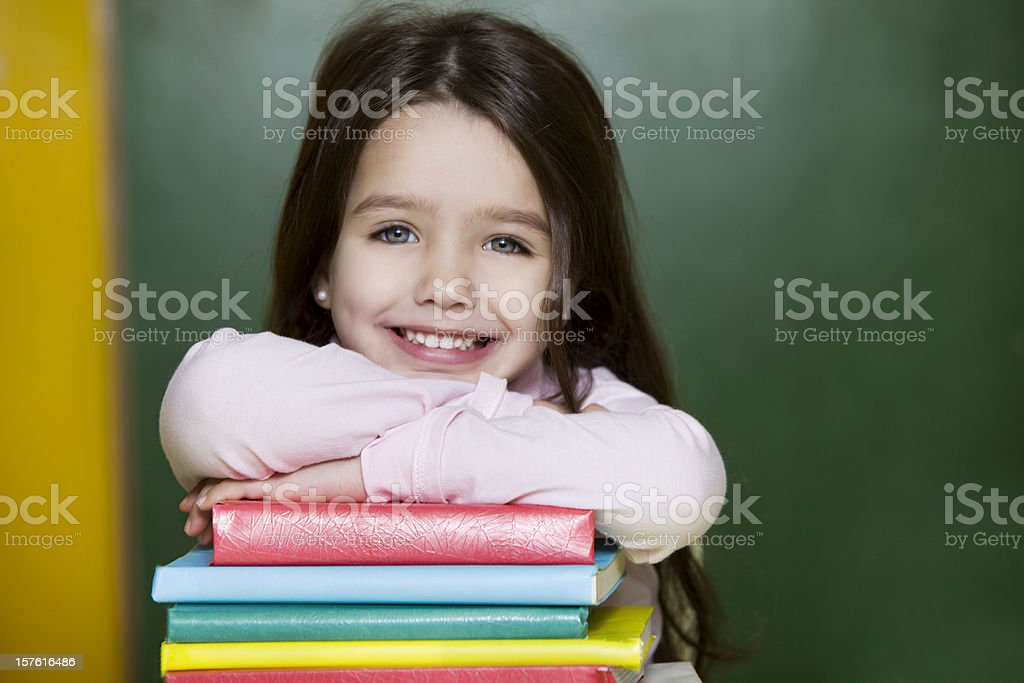 Little Girl Looking at Camera with Books royalty-free stock photo