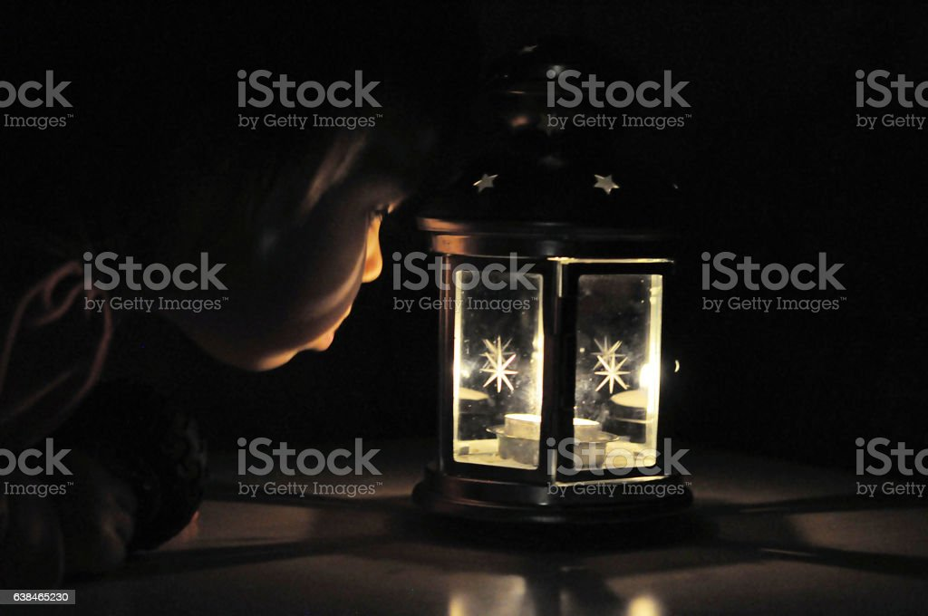 Little girl looking at candle light in lantern, high iso stock photo