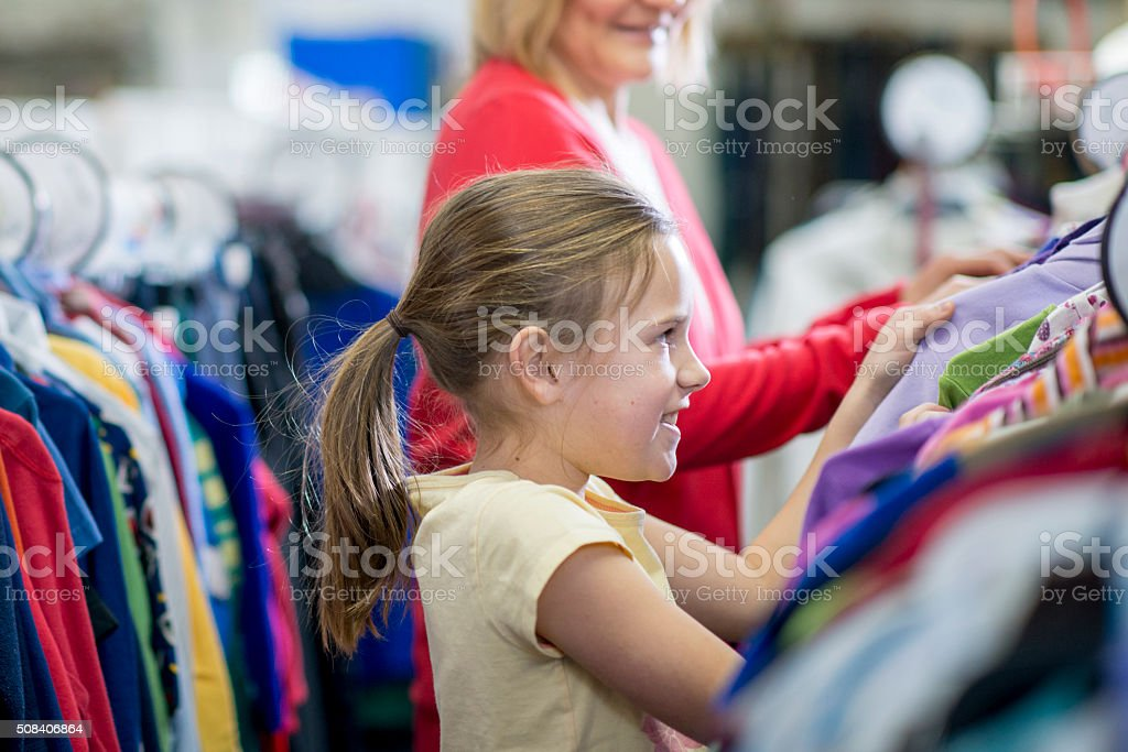Little Girl Looking at Clothes in the Store stock photo