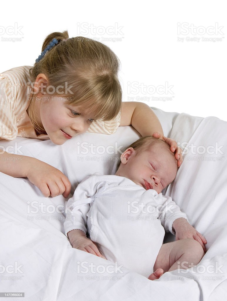Little girl looking at her newborn brother stock photo