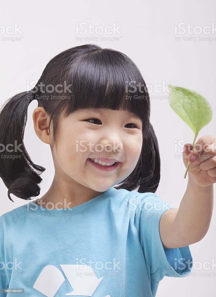 Little girl looking at leaf, close up studio shot royalty-free stock photo