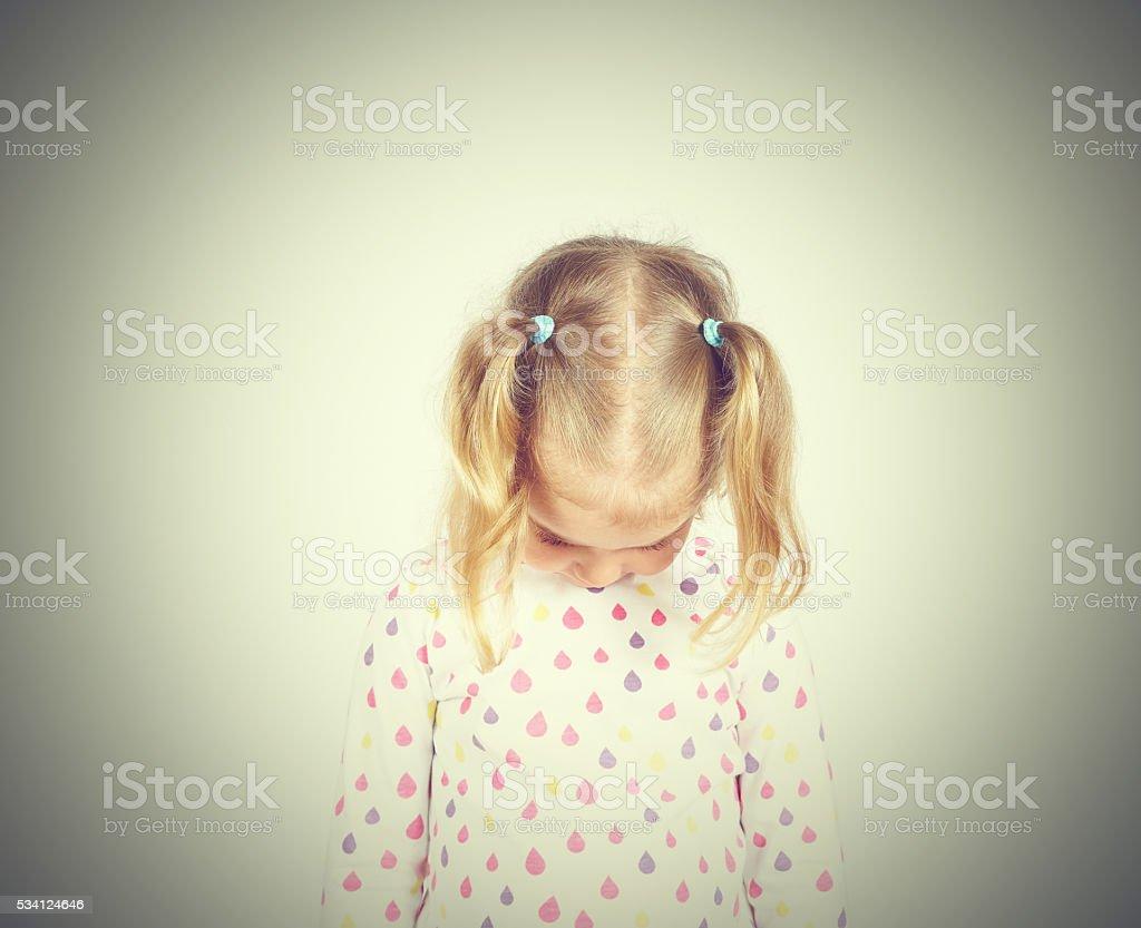 Little girl looking down hurt stock photo