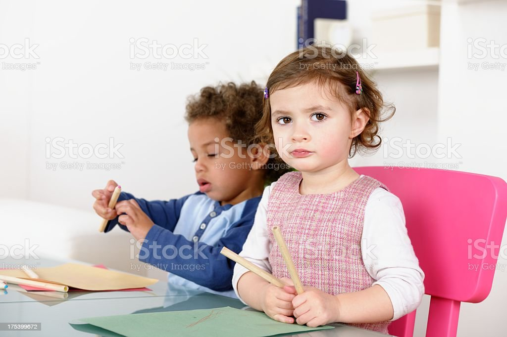 Little Girl Looking Puzzled While Peer Plays With Pencils stock photo