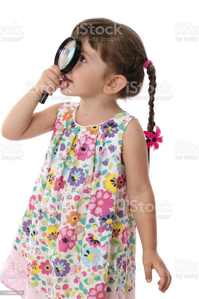 Little girl looking through a magnifying glass royalty-free stock photo