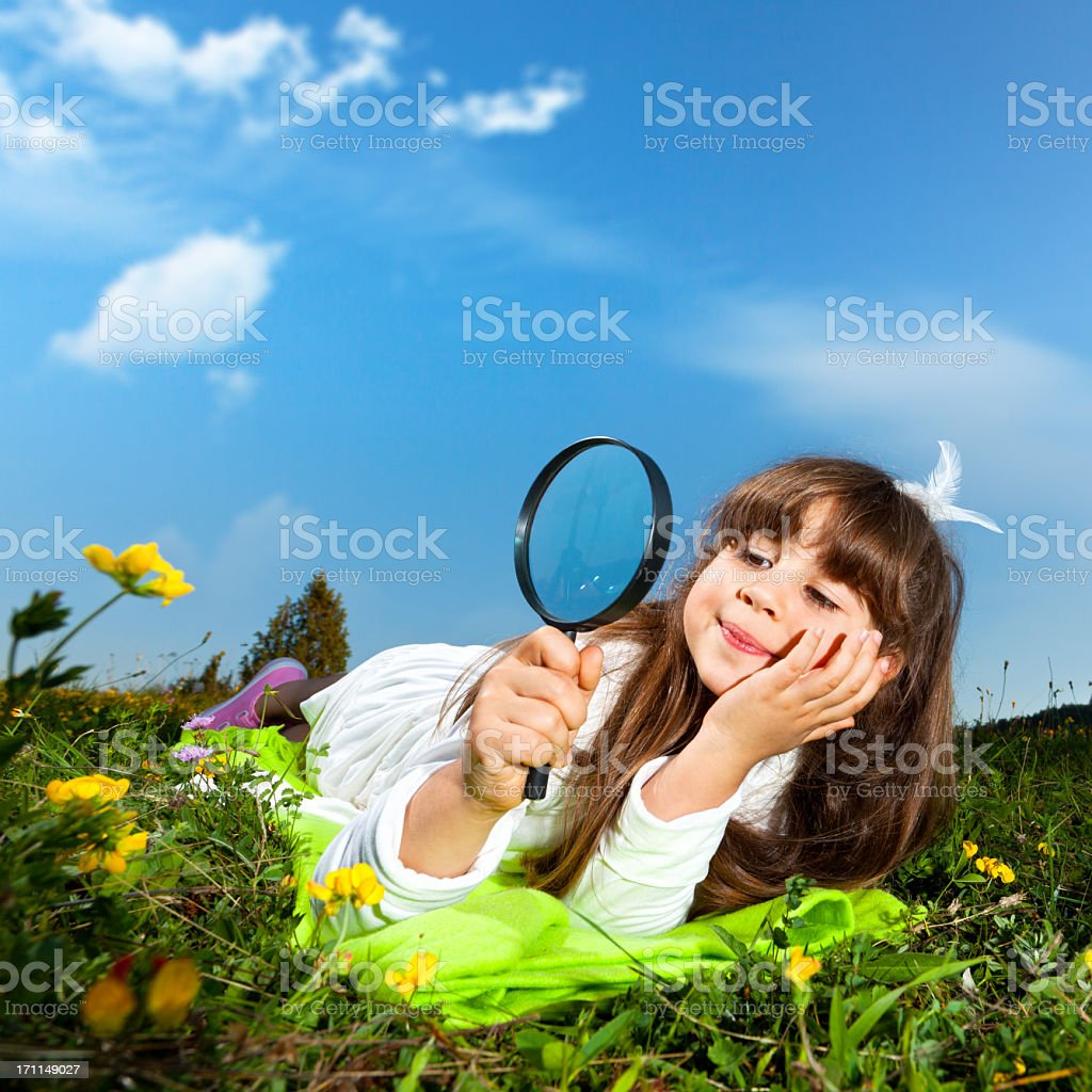 Little girl looking through magnifying glass royalty-free stock photo