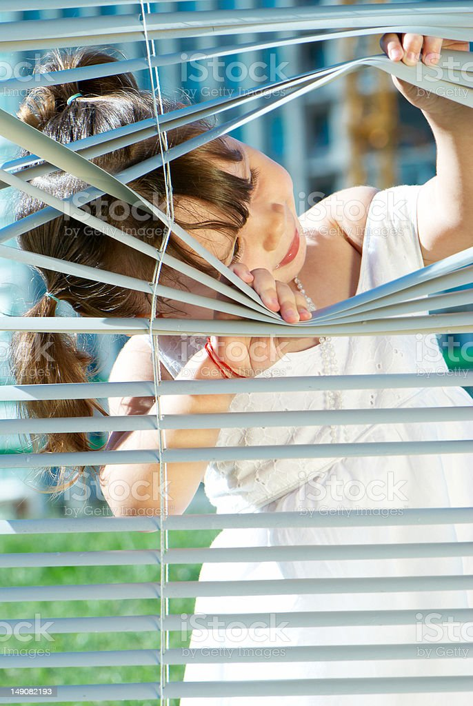 little girl looking through the blinds royalty-free stock photo