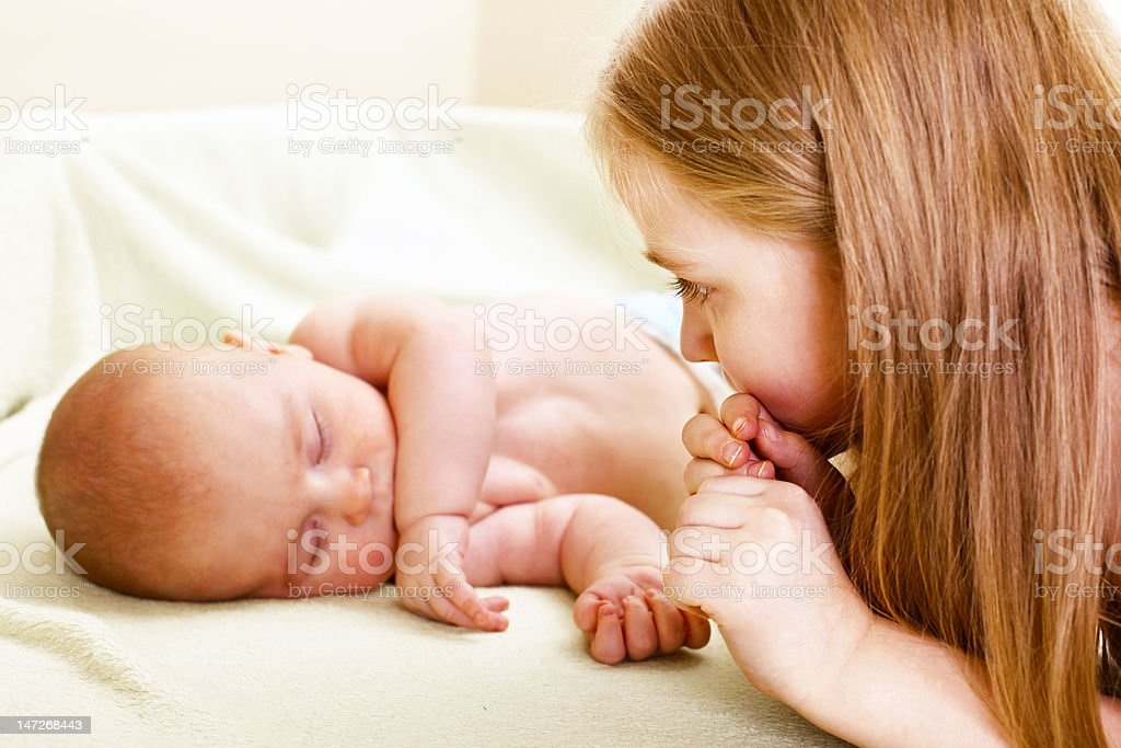 little girl looking to new sibling royalty-free stock photo