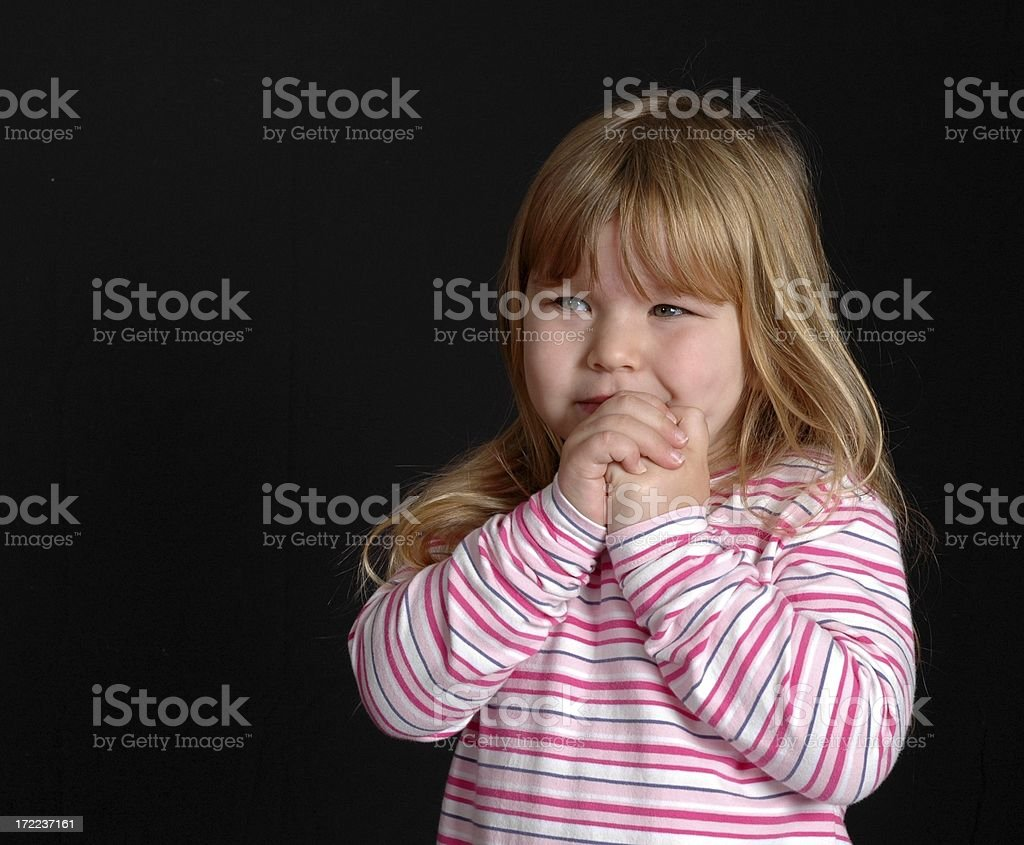 Little girl looking worried and alone on a black background royalty-free stock photo