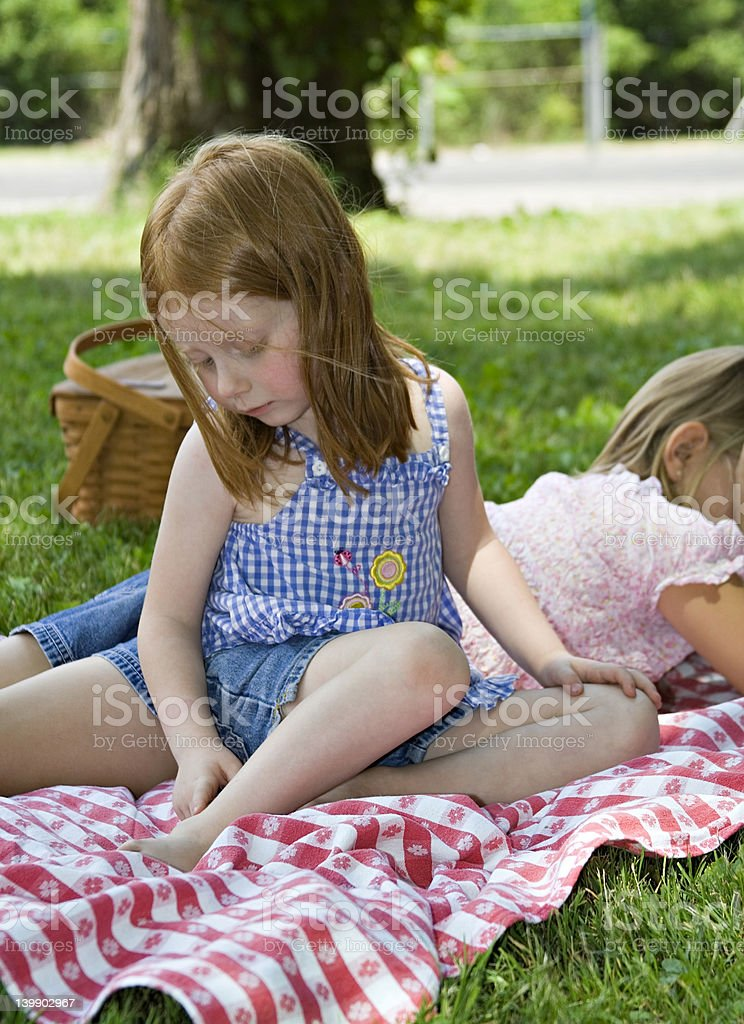 Little girl looks at a mosquito bite during a picnic stock photo