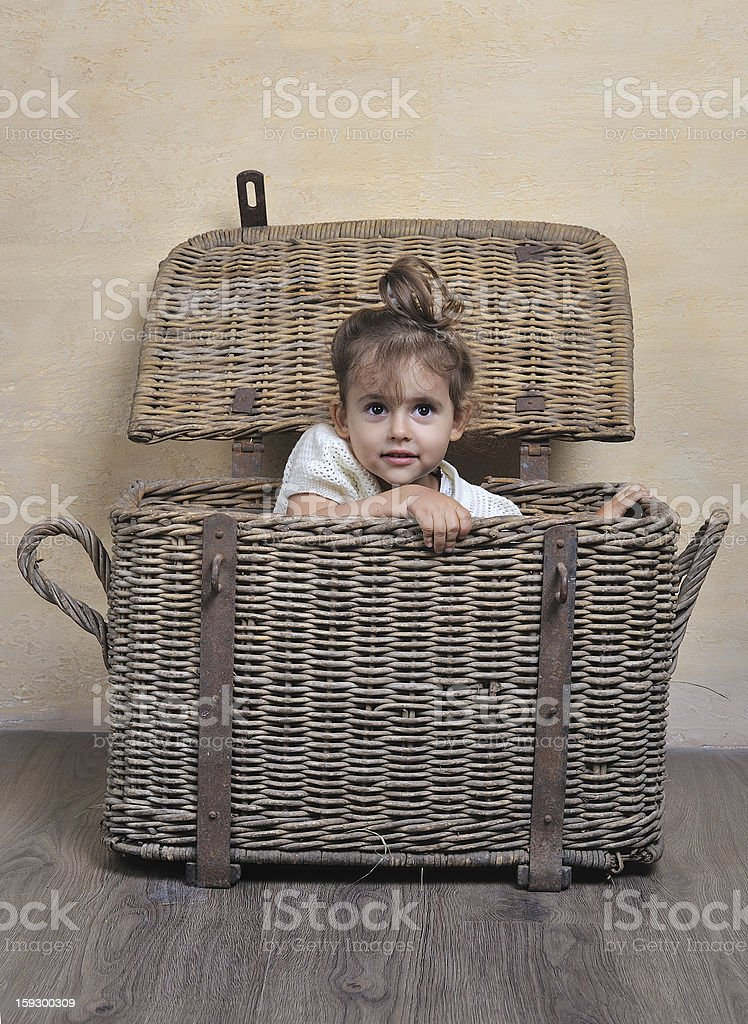 Little girl looks out of a wicker basket. royalty-free stock photo
