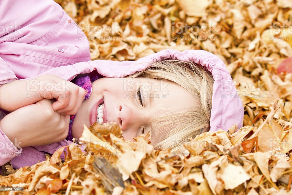 Little Girl Lying in Autumn Leaves royalty-free stock photo