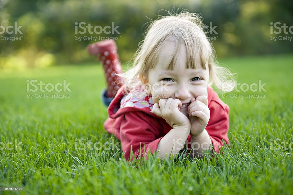 Little girl lying on front and smiling. royalty-free stock photo