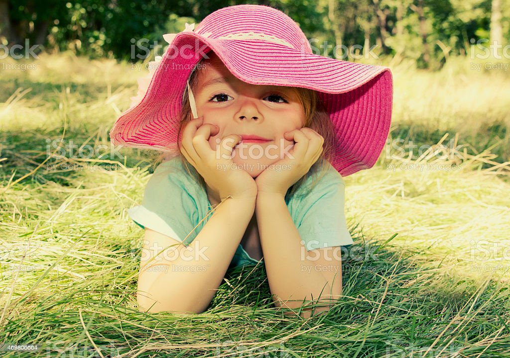Little girl lying on grass outdoor. Smiling girl face closeup. stock photo