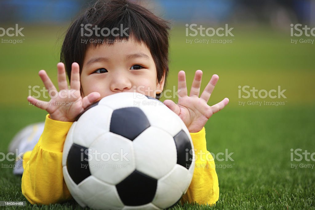 Little Girl Lying On Lawn With Soccer Ball royalty-free stock photo