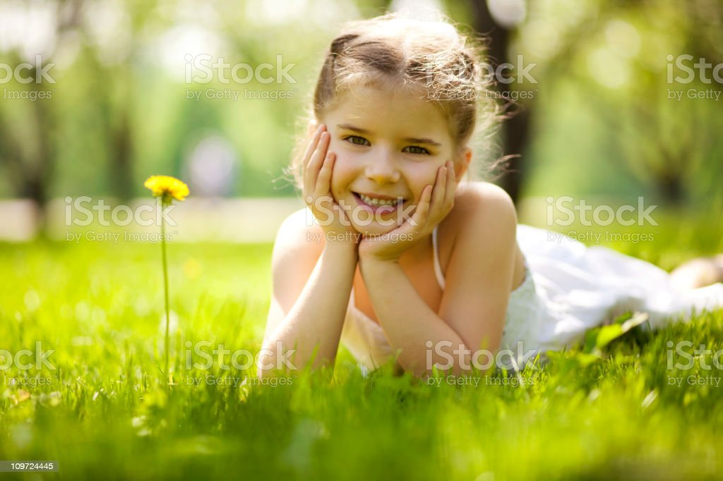 Little girl lying on the grass and looking at the camera royalty-free stock photo