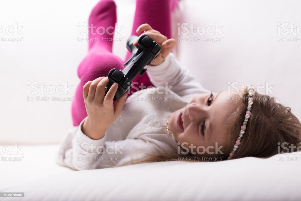 Little girl lying playing with a game controller stock photo
