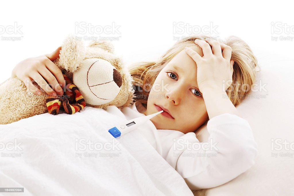 Little girl lying sick in her bed with teddy bear. royalty-free stock photo