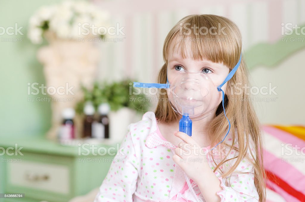 little girl makes inhalation home stock photo