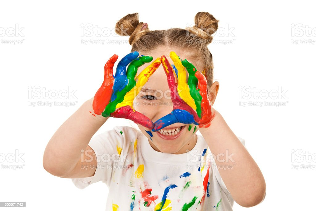 Little girl making a face with hands covered with paint stock photo