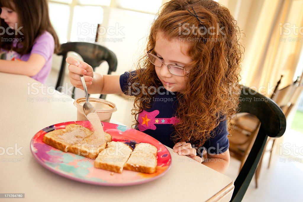 Little Girl Making Cinnamon Toast in Kitchen of Her Home royalty-free stock photo
