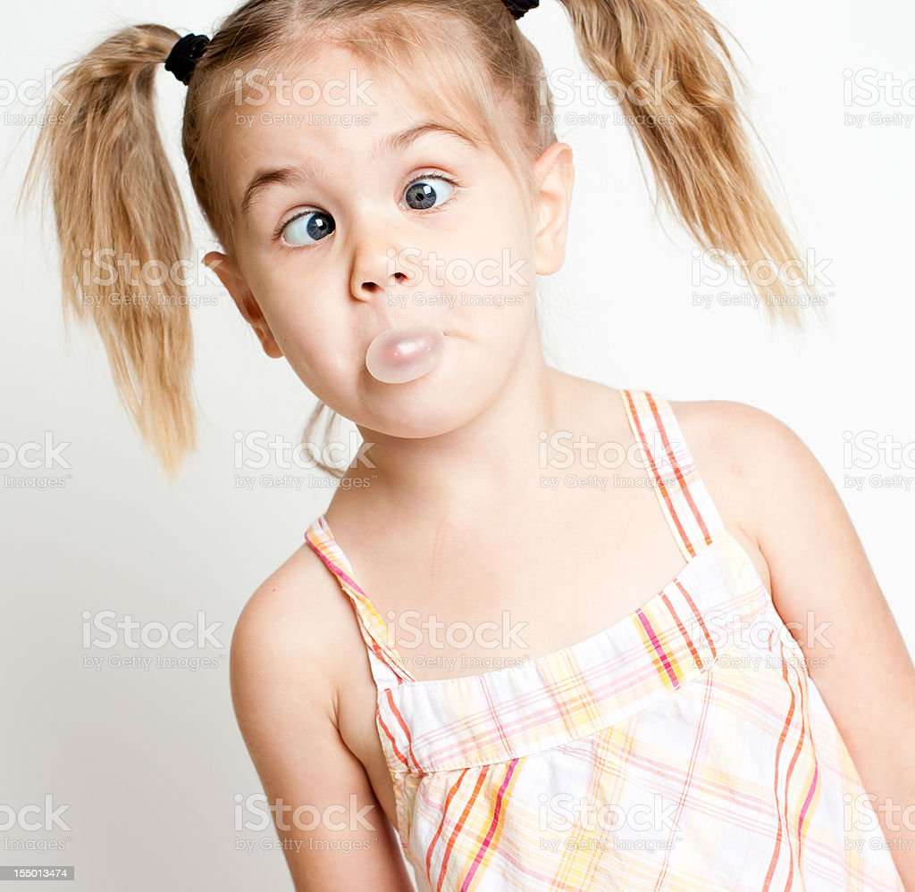 Little Girl Making Cross Eyes While Trying to Blow Bubbles royalty-free stock photo