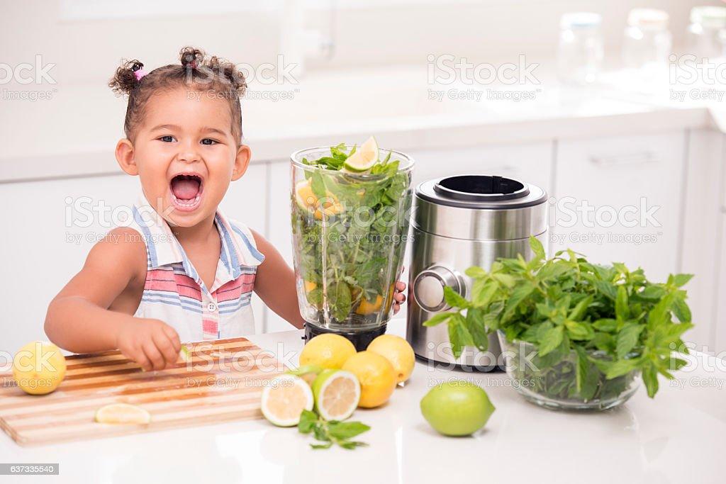 Little girl making fresh lemonade. stock photo