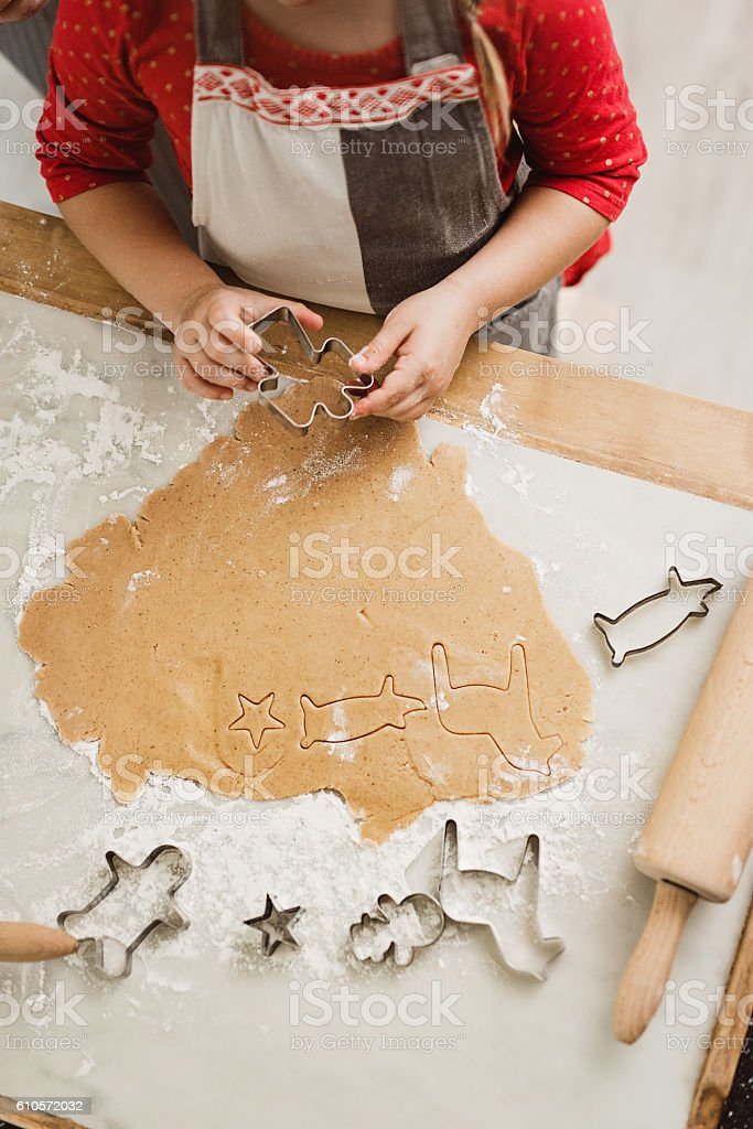 Little girl making gingerbread cookies for christmas stock photo