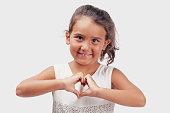 Little girl making heart shape with hands