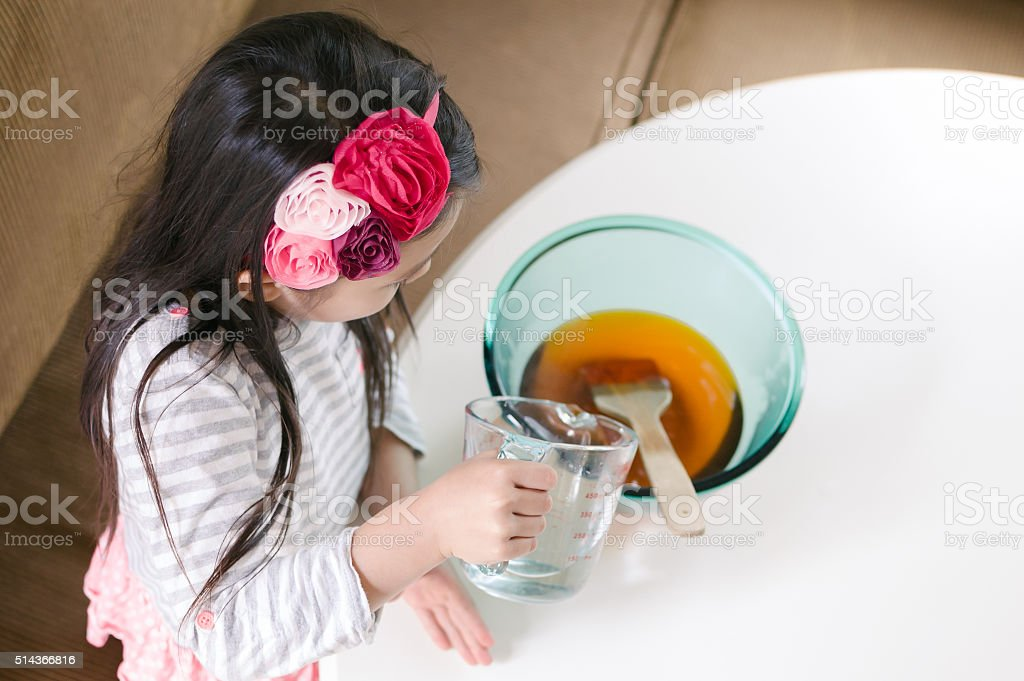 Little girl making jello in the kitchen stock photo