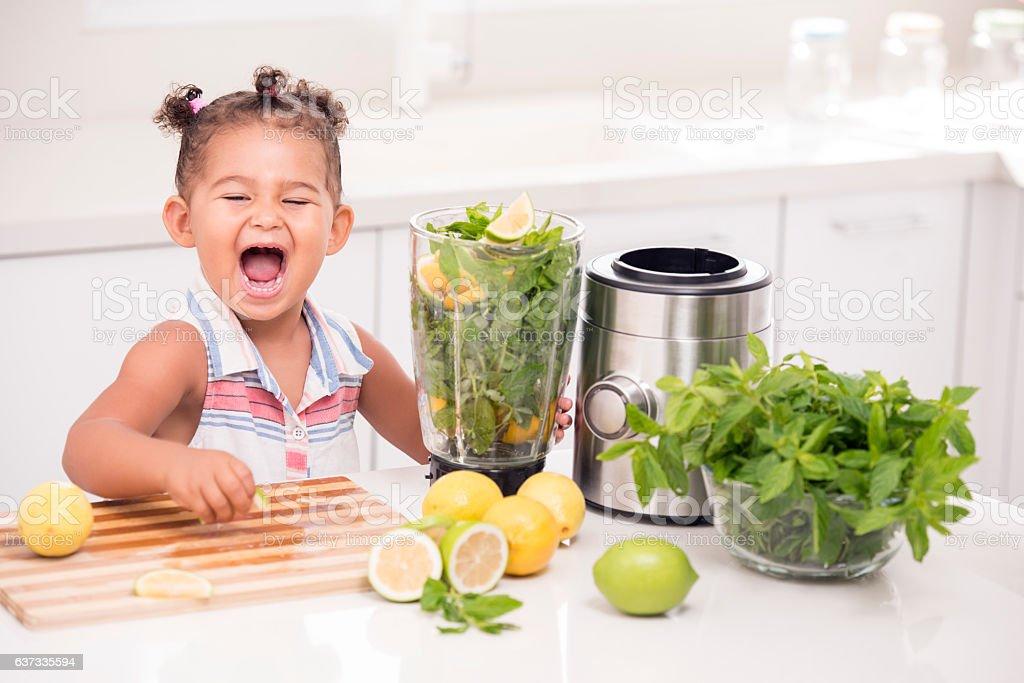 Little girl making lemonade. stock photo