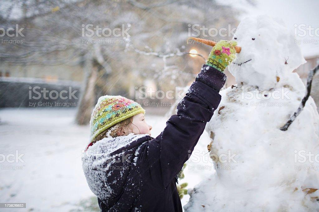 Little girl making snowman royalty-free stock photo