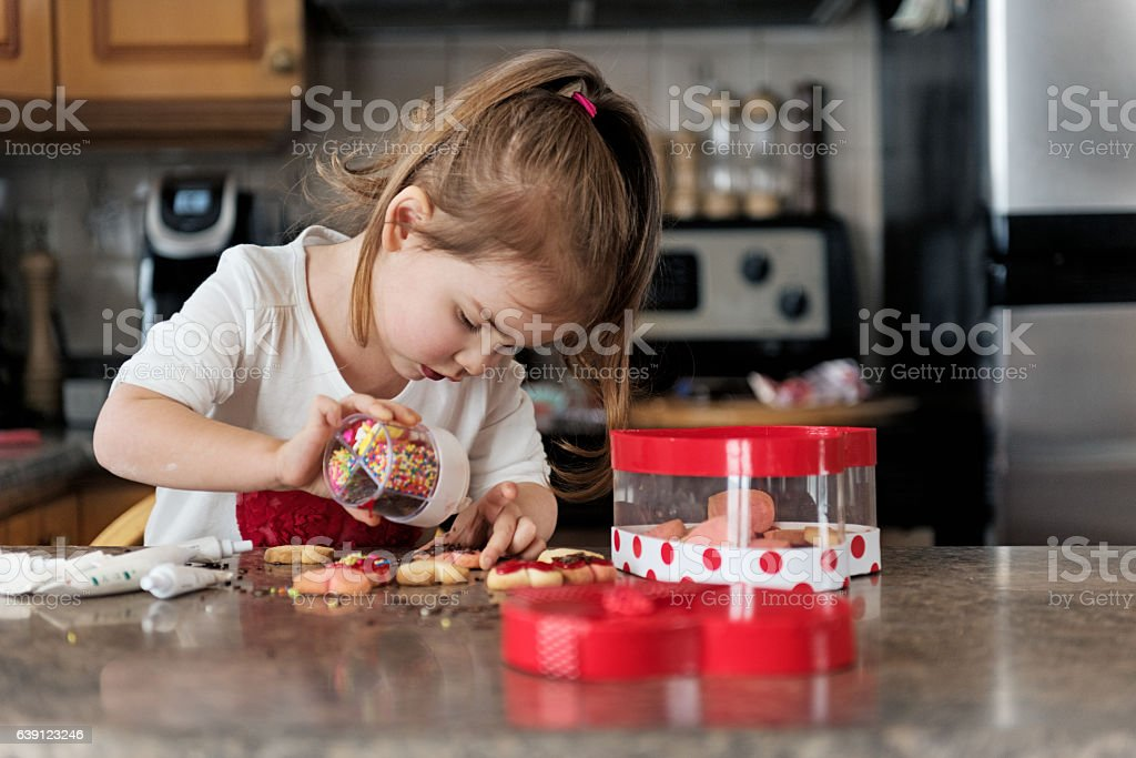 Little girl making valentine's cookie stock photo