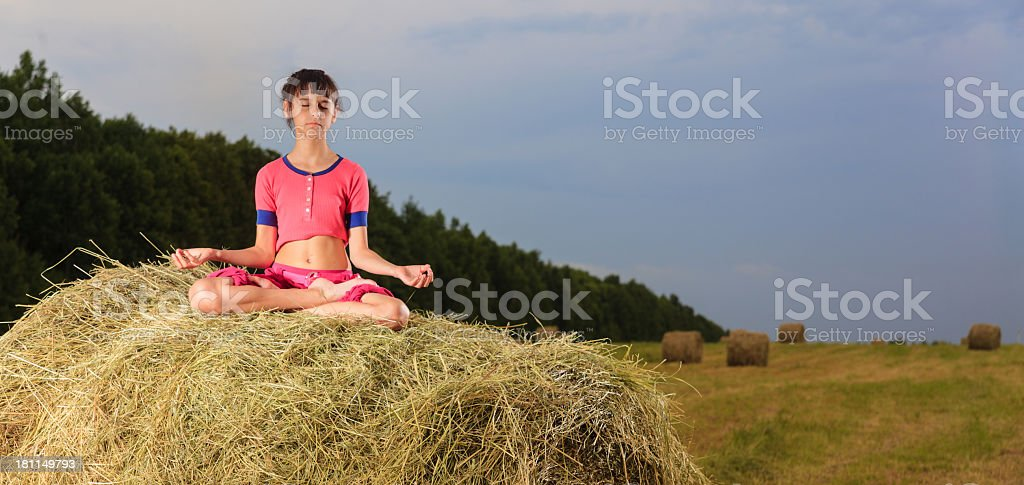 Little girl meditate on a hay bale royalty-free stock photo